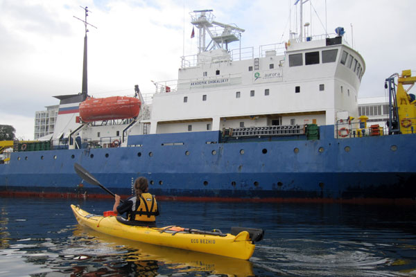 Isaac paddling past a Russian research ship in Hobart Docks